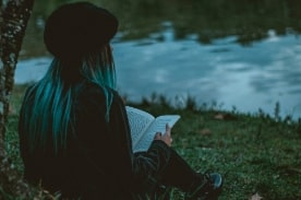 girl reading by a pond.